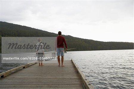 Junge (9-11 Jahre) und Vater tragen Rückansicht Tackle am Bootssteg, Angeln