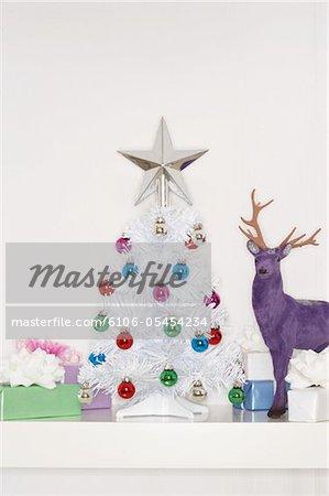 Kleine gefälschte umgeben von Geschenken und Rentier, Weihnachtsbaum hautnah