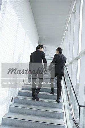 Deux hommes d'affaires, monter les escaliers, vue arrière