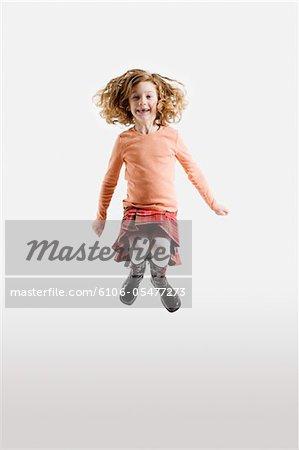 Fille (6-7) sautant dans les airs, sourire, portrait
