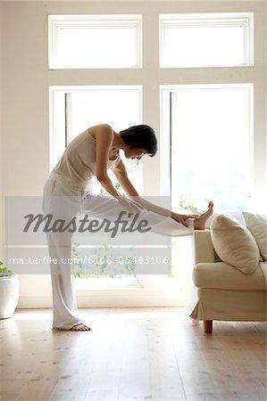 Junge Frau, die Dehnung der Beine auf dem Sofa im Wohnzimmer