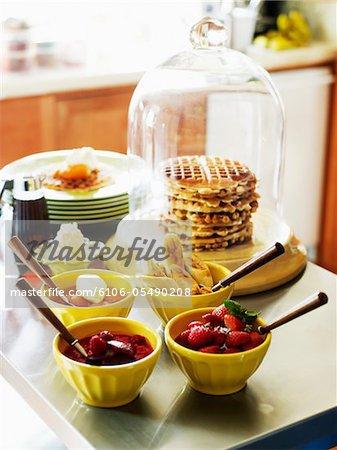 Pile de gaufres avec des garnitures assorties en bols - fraises fraîches, les pêches avec la crème fouettée, bananes et noix et compote de petits fruits