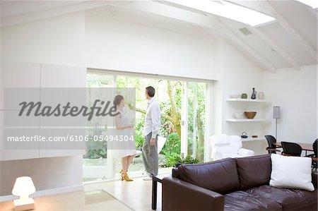 Mann und Frau suchen aus Fenster im Wohnzimmer.
