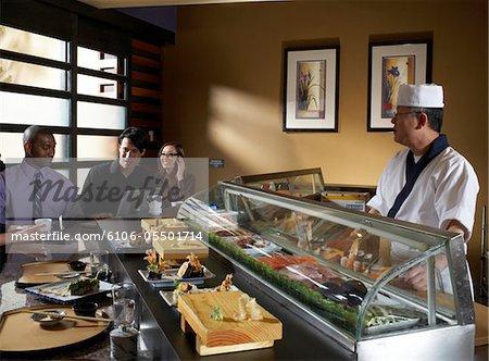 Gruppe von Menschen sitzen in der Sushi-Bar, Kellner hinter der Theke, ein Mann mit laptop