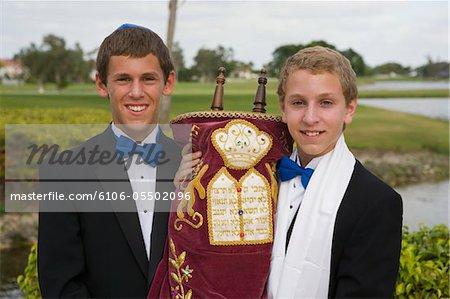 Deux adolescents tenant la Torah en plein air au cours de la célébration de la Bar-mitsvah, portrait