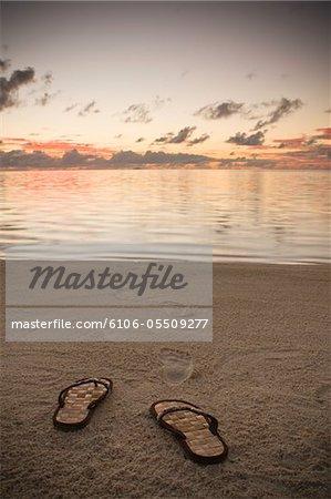 Französisch Polynesien, Bora Bora, Sandalen und Fuß druckt im Sand am Strand in der Abenddämmerung