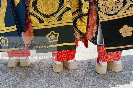 Japon, Kyoto, trois femmes portant des kimonos permanent en ligne, vue arrière, partie basse