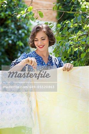Femme suspendue de feuilles sur la corde à linge