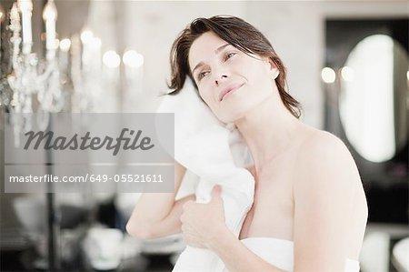 Femme séchant ses cheveux dans la chambre