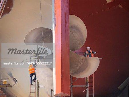 Travailleurs examinant les turbines de navire sur site