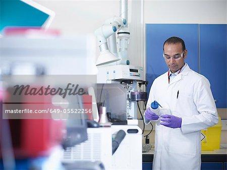 Scientist putting liquid in beaker