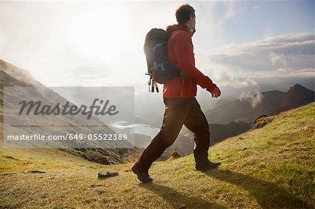Hiker walking on grassy mountaintop