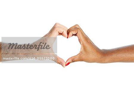 Couple de race mixte en forme de coeur avec les mains