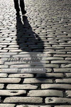 Schatten der Person auf Kopfsteinpflaster, London, England