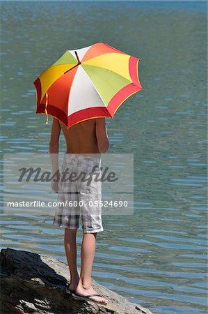 Retour vue du garçon à l'aide de parapluie de soleil, Alpes, France
