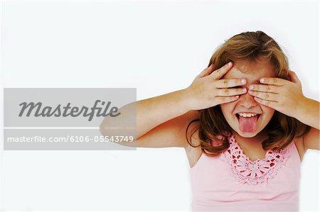 Fille (8-10) piquer tire la langue, tandis que la lecture à travers les doigts, gros plan