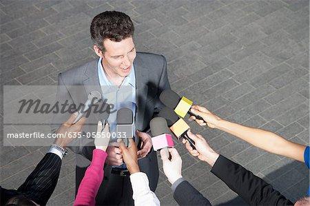 Journalistes tenant des microphones pour le politicien