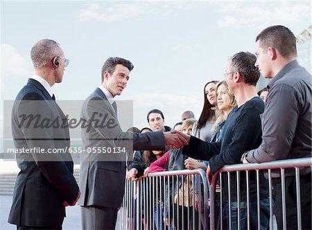 Politicien serrant la main de gens derrière la barrière