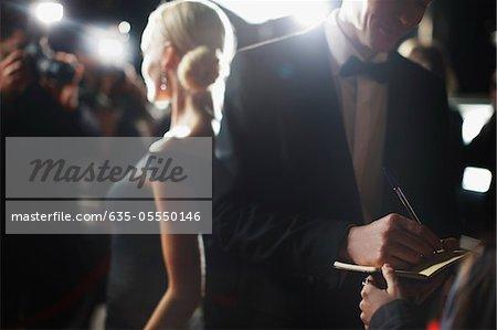 Célébrité, signer des autographes sur tapis rouge