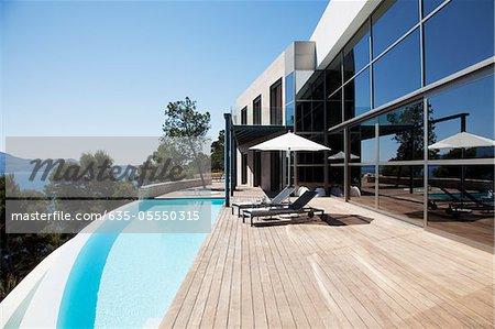 Chaises longues et piscine à l'extérieur de la maison moderne