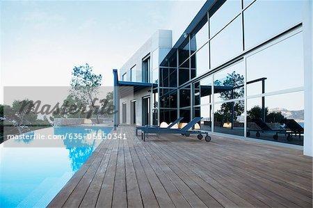 Chaises longues et piscine à débordement à l'extérieur de la maison moderne
