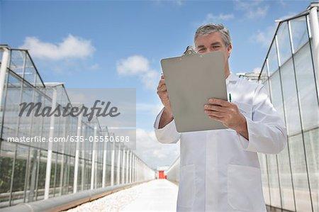 Scientifique écrit dans le presse-papiers à l'extérieur des serres