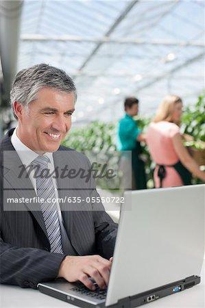 Homme d'affaires travaillant sur ordinateur portable à effet de serre