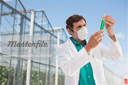Scientist in mask examining liquid in test tube
