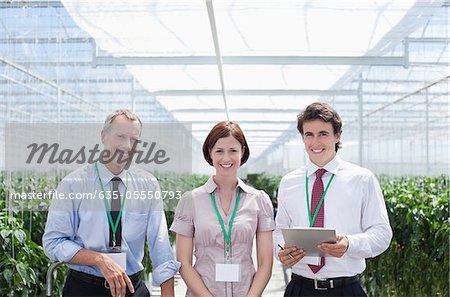 Travailleurs debout ensemble dans la serre