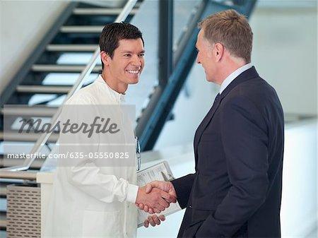 Homme d'affaires lui serrer la main avec le chercheur