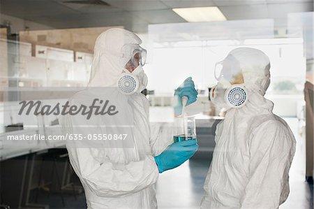 Wissenschaftler in Schutzausrüstung setzen Flüssigkeit im Becherglas im Labor