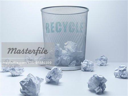 Balles froissés de papier à côté de bac de recyclage