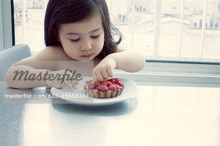 Kleine Mädchen essen Himbeer Torte