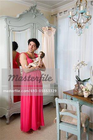 Drag queen wearing nightwear holding doll