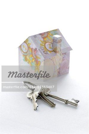 Bündel von Schlüsseln und Musterhaus gefaltet mit britischen Pfund-Banknoten