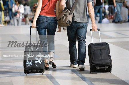 Couple marchant en plein air avec des bagages