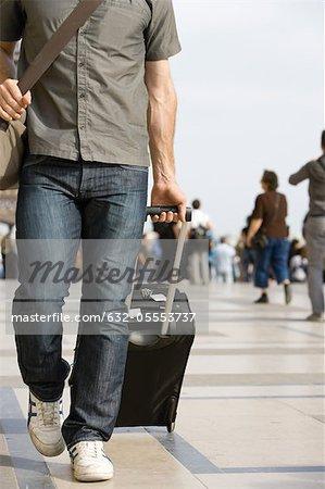 Mâle voyageur à pied avec bagages, recadrée