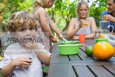 Garçon bénéficiant d'une collation en plein air avec sa famille
