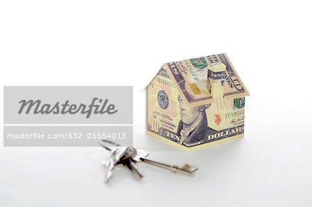 Musterhaus gefaltet mit Dollarnoten und Tasten