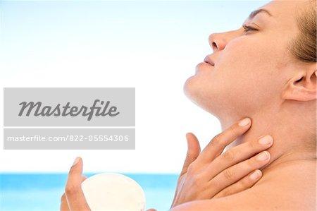 Jeune femme, application de crème hydratante sur le cou