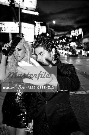 Paar Walking City Street at Night Abschirmung ihre Gesichter