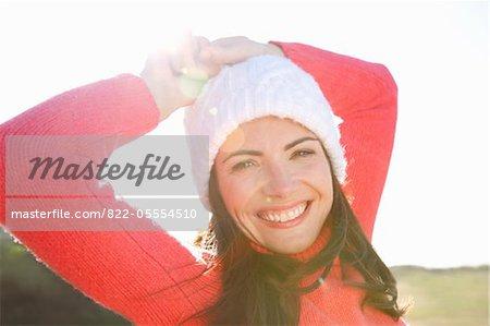 Femme souriante avec les mains sur la tête coiffé de Wollen