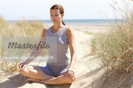 Frau praktizieren Yoga auf Sanddüne vom Ozean