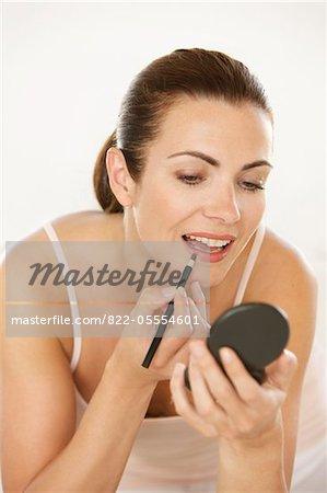 Woman Holding Compact Using Lipstick Brush