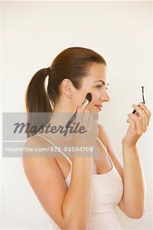 Femme tenant Compact appliquer fard à joues