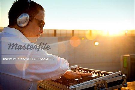 DJ en utilisant la Console de mixage au lever du soleil