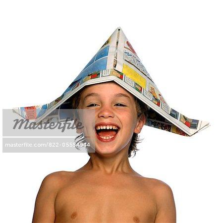 Garçon portant chapeau journal rire