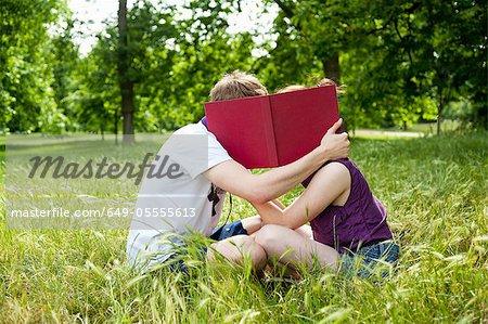 Jugendliche versteckt sich hinter dem Buch im park