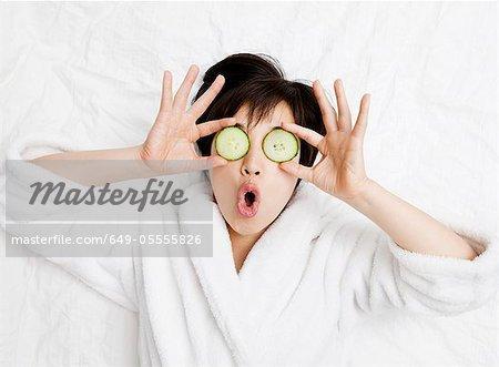 Femme en peignoir avec concombres sur les yeux
