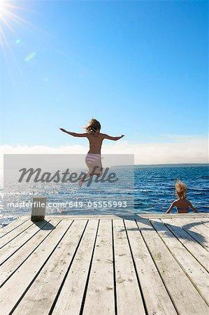 Jeunes filles sautant dans le lac